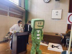 司会中の田村運営専務と国税庁マスコットキャラクター「イータ君」